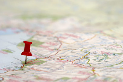 A push pin is inserted on a travel destination of a map.
